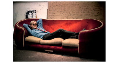 Andy Warhol at 47th street Factory,  poses on notorious Factory red couch with Jackie Kennedy silkscreen.1965 New York City